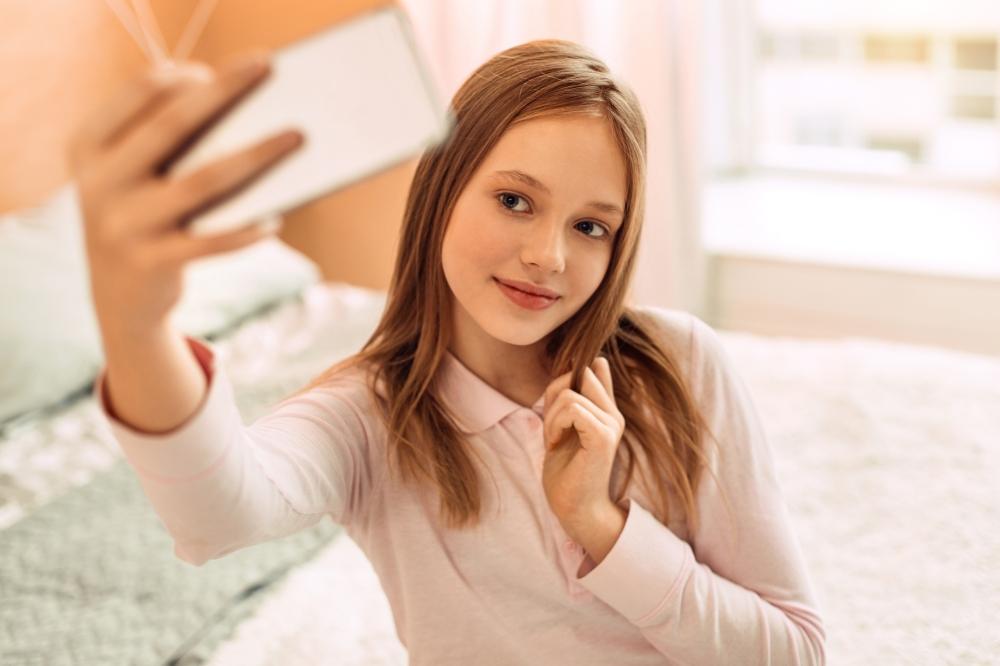 Pretty teenage girl posing while taking selfies