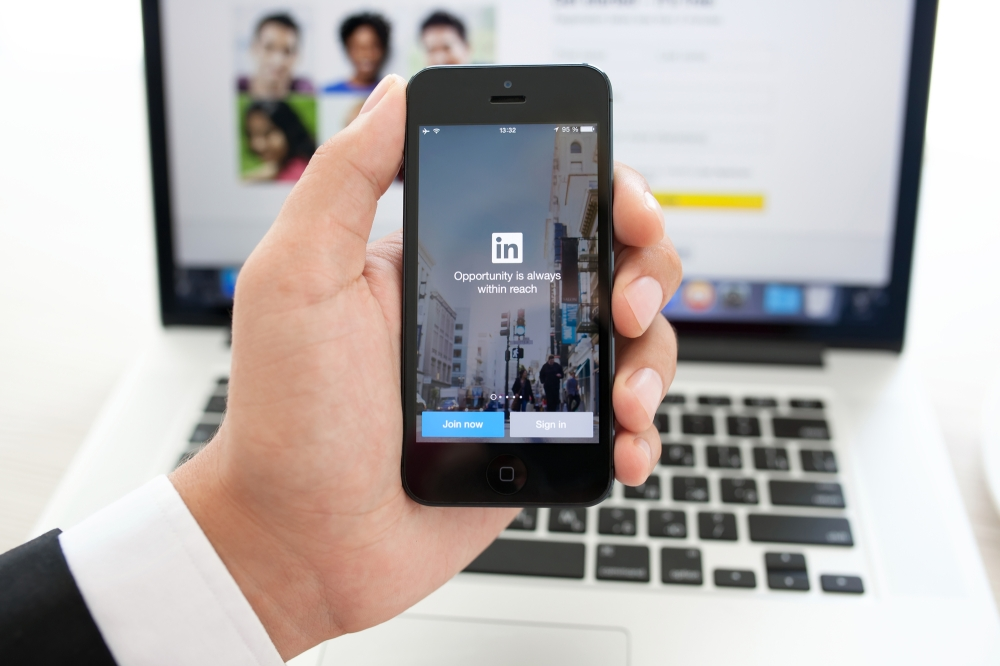 businessman holding iPhone with app LinkedIn on the screen on a